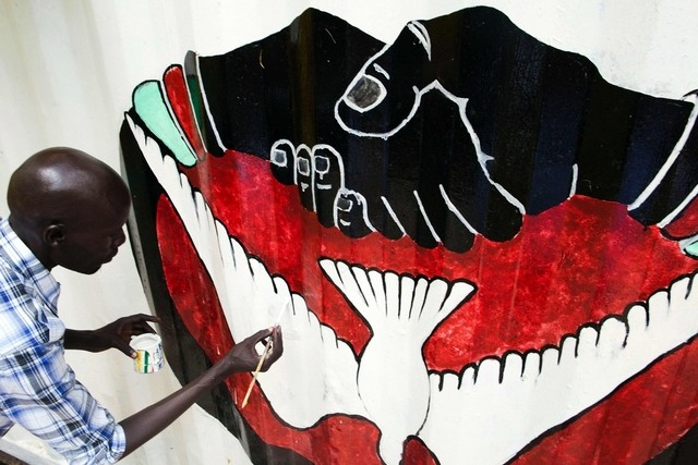 A member of the new activist movement #AnaTaban, paints a new mural at the Aggrey Jaden cultural centre in Juba, South Sudan, on September 18, 2016. #AnaTaban was founded recently by 40 young South Sudanese artists who are calling for an end to civil conflict through the arts. Albert Gonzalez Farran / AFP