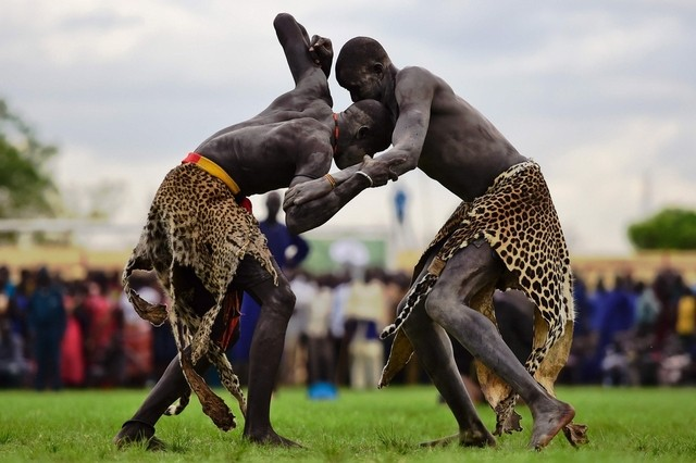 "Wrestlers from Jonglei and eastern lakes region take part in the South Sudan national wrestling competition for peace at Juba stadium, South Sudan, on April 20, 2016. South Sudan is holding a ""wrestling for peace"" tournament, bringing together athletes from around the country. Carl de Souza/AFP"